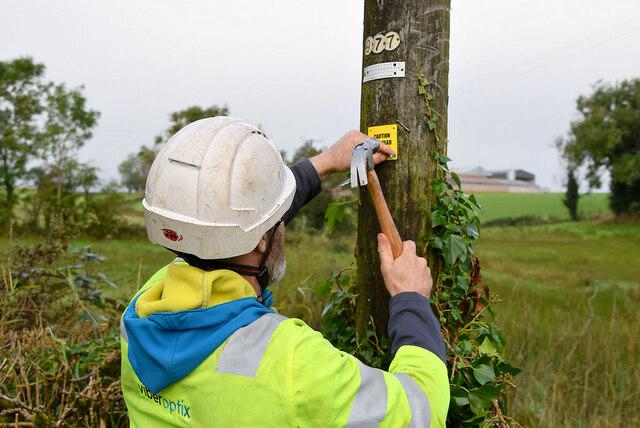 Fitting a fibre notice to pole,  Ardatinny