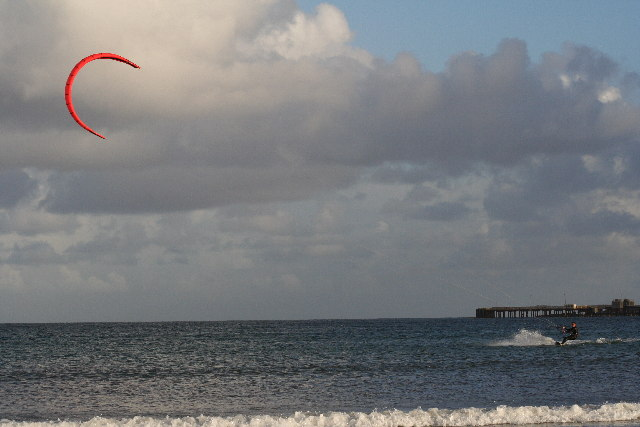 Kitesurfer out at sea in front of pier