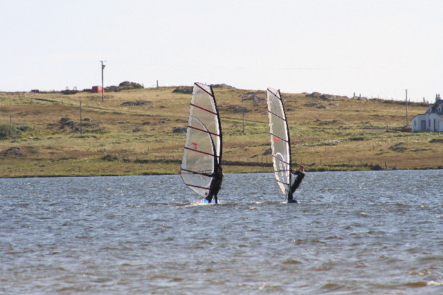 Two people windsurfing
