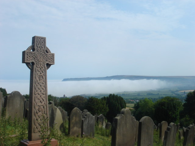 Graveyard of St. Stephen's church and mist over Robin Hood's Bay.
