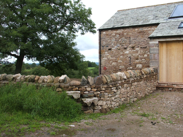 Stile and converted barn.