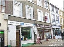 SH4862 : Y Llechen Credit Union and Harrop's Optometrist  in Upper Pool Street by Eric Jones