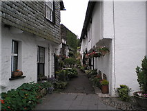 SD3598 : Narrow Lane in Hawkshead Village with pots and hanging baskets in bloom by Keith Fairhurst