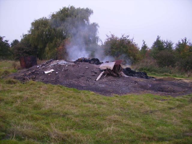 Smouldering bonfire on rubbish tip