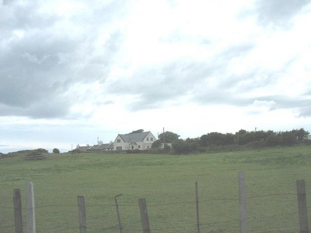 View across rough pasture towards the former Siloam Chapel at Llanfair-yn-Neubwll