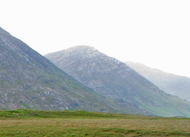 Grassy plain with stony mountains beyond