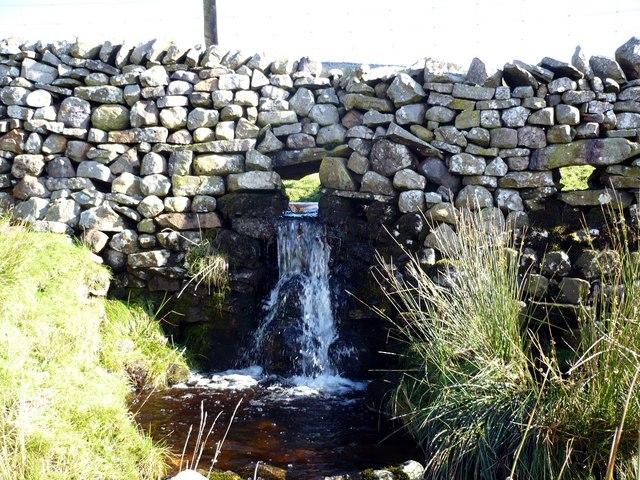 Waterfall passing through dry stone wall.